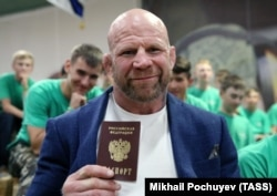 Former MMA fighter Jeff Monson poses with his Russian passport for photographers in Moscow earlier this year.