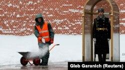 Un muncitor presoară sare în fața zidului Kremlinului
