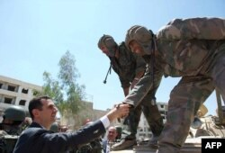 Сирия президенті Башар Асад үкімет сарбаздарымен амандасып тұр. 1 тамыз 2013 жыл.