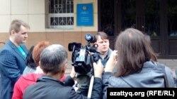 Журналист Александр Баранов (в центре), привлекаемый к уголовной ответственности по обвинению в клевете, дает интервью у здания суда. Павлодар, 11 мая 2016 года.