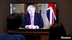 Деца слушат обръщението на британския премиер Борис Джонсън, който обяви по-строги мерки за социална дистанция през следващите 3 седмици