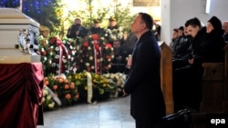 Polish President Andrzej Duda (center) prays at the coffin of Lukasz Urban during a funeral Mass in Banie in northwestern Poland on December 30.