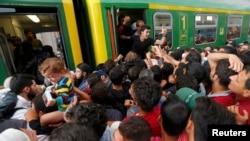 Мигранты штурмуют поезд на вокзале Будапешта, 3 сентября 2015 года.