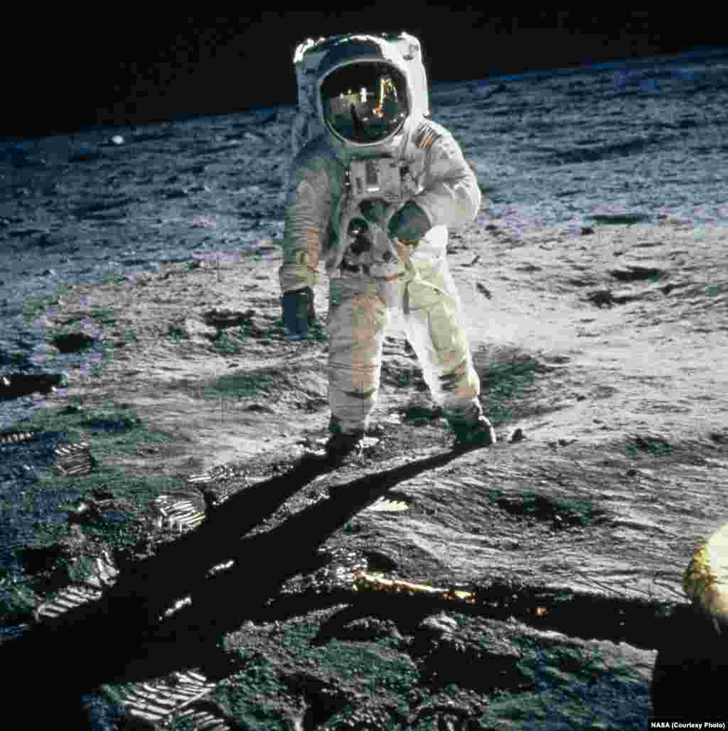 "Astronaut Buzz Aldrin walks on the moon's Sea of Tranquility, his visor reflecting Neil Armstrong and the lunar module ""Eagle."" The Apollo 11 astronauts carried the National Geographic Society flag with them on their journey to the moon."