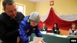 A man with his child casts his vote at a polling station during parliamentary elections in Przecieszyn, south Poland on October 25.