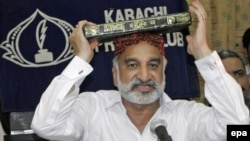 Zulfiqar Mirza, a senior minister in the southern Sindh Province, holds the Koran aloft as he announces his resignation from the government