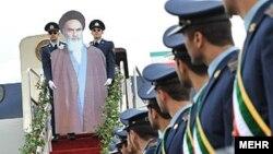Khomeininin kartondan düzəldilmiş siluetini ciddi şəkildə təyyarənin pilləkənləri ilə aşağı endirirlər