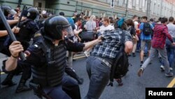 Police chase protesters during a rally against planned increases to the nationwide pension age in Moscow on September 9.