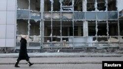 Иллюстративное фото. Женщина проходит вдоль разрушенного здания. Донецк, Февраль 2015 года