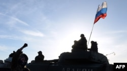 A Russian flag flew above pro-Russia militants sitting atop a self-propelled howitzer in late February, as they took a break in moving from the front line near the eastern town of Starobeshevo, in Donetsk region.