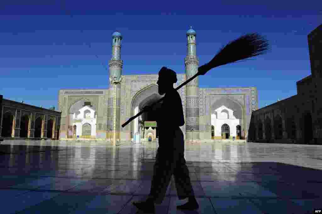 A man carries a broom as he walks past the main mosque in Herat, Afghanistan, during Ramadan. (AFP/Aref Karimi)