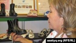 Женщина рассматривает обувь казахстанского производства. Астана, 21 ноября 2012 года.