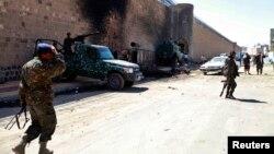 Йеменские полицейские у стен тюрьмы, где произошли взрывы. Сана, 14 февраля 2014 года.