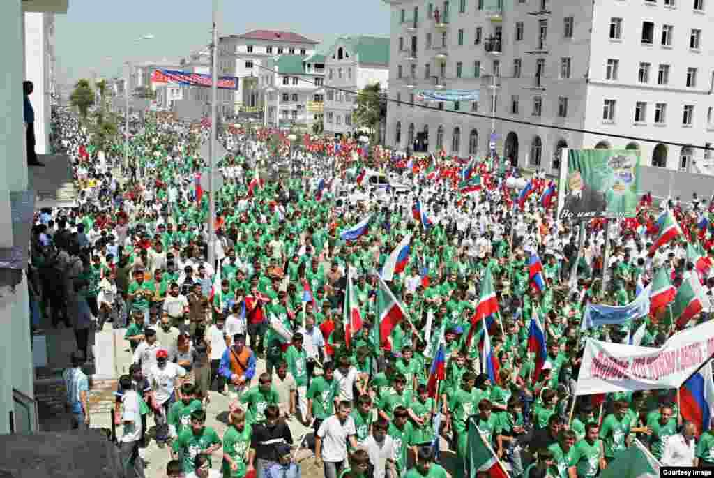Толпа людей с изображением Рамзана Кадырова на одежде.