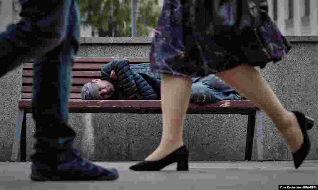 Люди проходят мимо человека, спящего на скамейке на одной из улиц Москвы, Россия