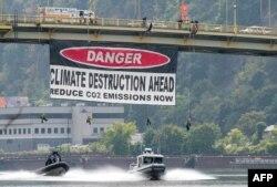 """Greenpeace-aktivisták molinója – """"Vigyázat, klímapusztítás következik, csökkentsük a szén-dioxid-kibocsátást most!"""" – a pennsylvaniai Ohio folyónál, a G20-ak csúcstalálkozójának helyszínén, 2009. szeptember 23-án"""
