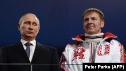 Президент России Владимир Путин и бобслеист Александр Зубков на церемонии закрытия Олимпийских игр в Сочи в 2014 году