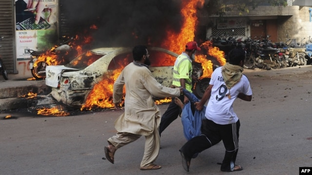 Pakistani volunteers and locals carry the dead body of a protester past a burning car after gunmen opened fire on a rally in Karachi on May 22.