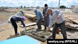 Люди строят дома в селе Курайлы под Актобе, где пострадавшим от паводков выделили земельные участки. Актюбинская область, 4 июня 2017 года.