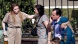 RUSSIA -- TATARSTAN -- Russia School Shooting -- A Russian emergency employee and a woman try to comfort a couple on their way to an ambulance at a school after a shooting in Kazan, Russia, Tuesday, May 11, 2021. Russian media report that some numbers of