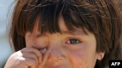 A girl cries outside her tent at a camp in Swabi after her family fled Swat.