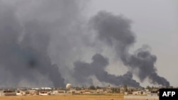 Smoke rises above the Baiji area as Iraqi pro-government forces take part in an operation to retake it from Islamic State militants.