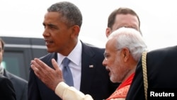 U.S. President Barack Obama (left) talks with India's Prime Minister Narendra Modi upon arriving in New Delhi on January 25.