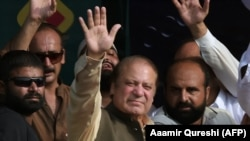 "Former Pakistani Prime Minister Nawaz Sharif (center) waves to supporters during a rally on his ""caravan of democracy"" protest drive."
