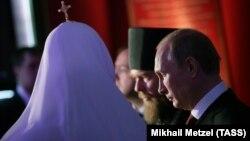 Владимир Путин и патриарх Московский и всея Руси Кирилл (справа налево) на выставке о первой царской династии России.