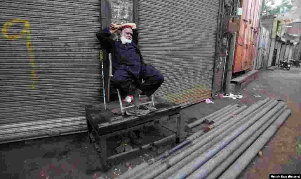 A worker in Lahore sits outside a closed shop during a country-wide strike by traders against government-imposed taxes. (Reuters/Mohsin Raza)
