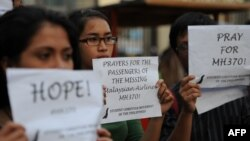 Philippines -- Students hold placards in solidarity with families of the passengers of the missing Malaysia Airlines flight MH370 plane during a candle light vigil at the university belt in Manila on March 13, 2014.