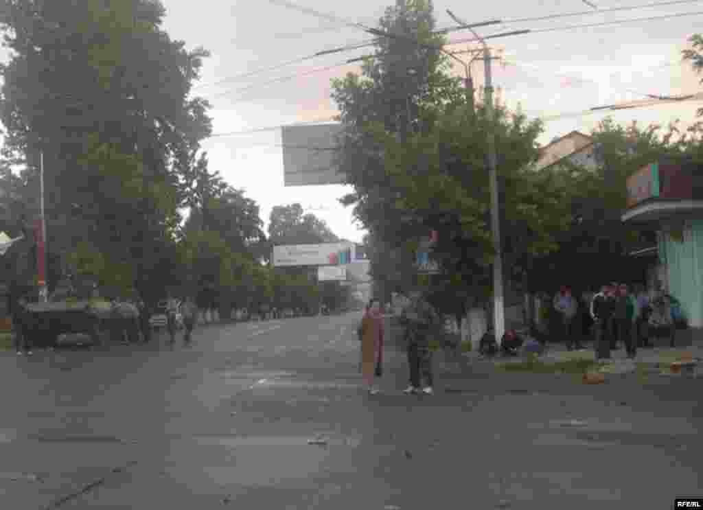Ош шаарынын көчөлөрүнүн биринде турган милиция кызматкерлери жана шаар тургундары. 11-июнь, 2010-жыл.