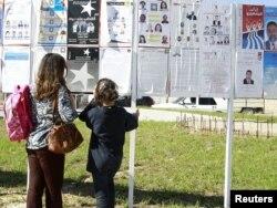 Тунисцы изучают предвыборные постеры. Тунис, 19 октября 2011 года.