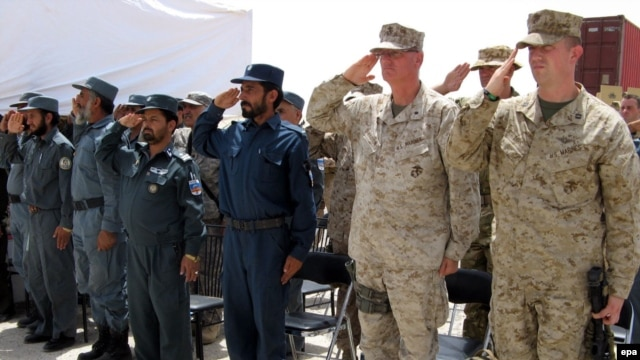 Afghan police and U.S. Marines salute during a ceremony marking conclusion of the Afghans' training.