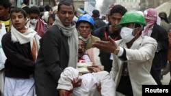 Antigovernment protesters carry an injured fellow protester in Sana'a on March 18, when dozens of demonstrators were said to have been killed by snipers.