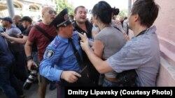 Влад Содель (в окулярах з фотоапаратом) і Ольга Сніцарчук (її тримає колега) одразу після побиття, Київ, 18 травня 2013 року