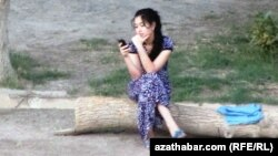 Mobil telefonly bir gyz. Arhiwden alnan illýustrasiýa suraty.