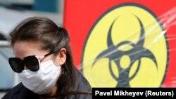 Коронавирус қаупі туралы баннердің жанында тұрған маска таққан қыз. Алматы, 24 наурыз 2020 жыл.
