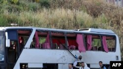 Police inspect the wreckage of a military bus after a roadside bomb detonated, killing at least four people.
