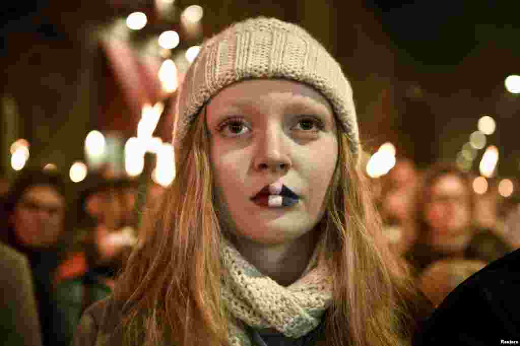 A girl with her lips painted in the French colours attends a commemoration event in front of the French Embassy in Copenhagen in memory of victims of the Paris attacks on November 13. (Reuters/​Nils Meilvang)