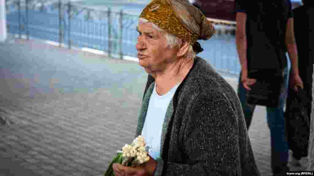 На центральній вулиці міста жінка продає цибулю –інгредієнт для літнього салату.