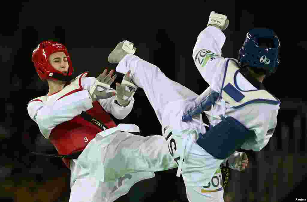 The United States' Paige McPherson (right) grapples with Azerbaijan's Farida Azizova in a preliminary round of the 67-kg women's taekwondo competition.