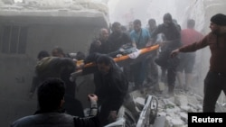 Residents and Civil Defense members carry the body of an elderly woman on a stretcher amid rubble of damaged buildings after an air strike on the rebel-held Al-Saliheen district in Aleppo on March 11.