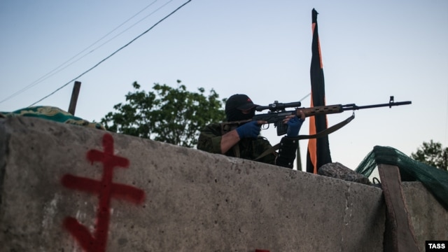 A pro-Russian sniper aims his rifle at a checkpoint near Slovyansk