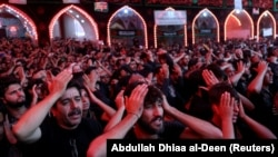 Shi'ite Muslim pilgrims commemorate the Arbaeen outside of Imam al-Hussein shrine in Karbala