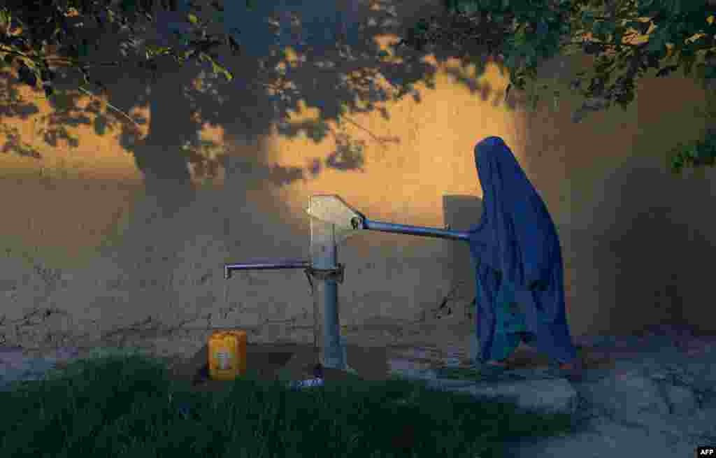 An Afghan woman collects water from a hand pump in Mazar-e Sharif in Ghazni Province. (AFP/Farshad Usyan)