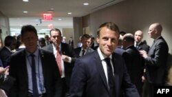 French President Emmanuel Macron, flanked by his advisors and security agents walk from one meeting to another at the United Nations headquarter on September 23, 2019, in New York