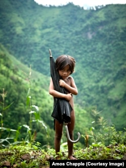 A small girl clutches an umbrella on a chilly day in the highlands of Nepal. Photo by Amos Chapple