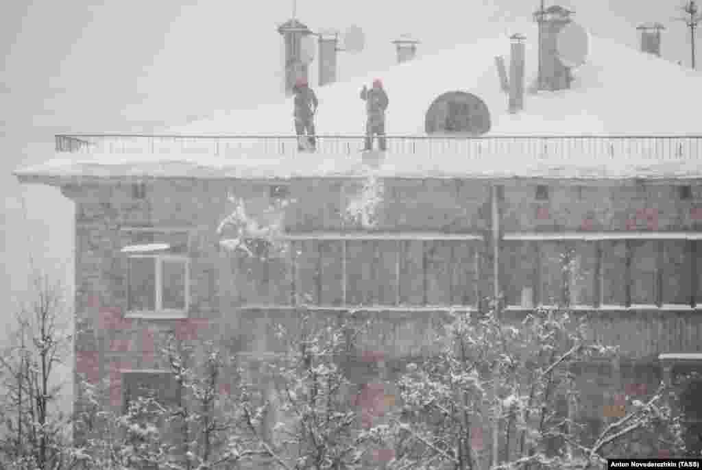 Сотрудники коммунальных служб на крыше во время снегопада