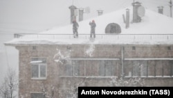 Men clear snow off a roof in Moscow on February 4.